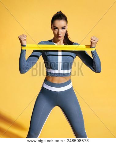 Sportswoman Performs Exercises For The Muscles Of The Hands. Photo Of Woman Workout With Resistance