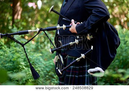 A Man With A Bagpipe, A Kilt In A Cage With A Green And Red Stripe. Culture