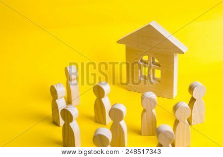 A Group Of Wooden Figures Of People Surround And Look At The Wooden House. Young People In Search Of
