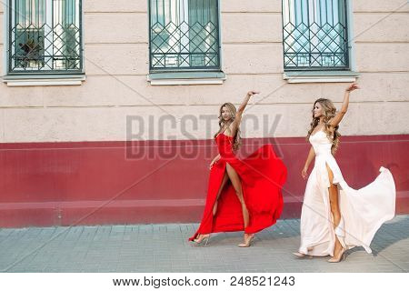 Two Confident And Fashionable Girls Wearing Elegant Evening Dresses. Slender Attractive Women With B