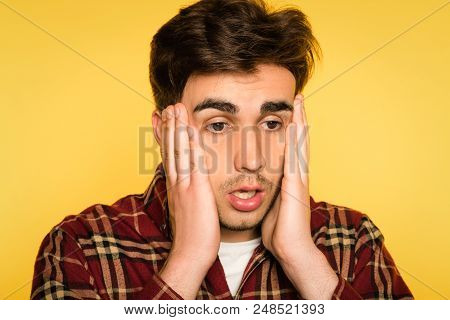 dumbfounded and taken aback man clutching his head and panicking. feelings of regret remorse and dismay. portrait of a young handsome brunet guy on yellow background. emotion facial expression. poster