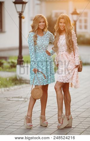 Two Gorgeous And Pretty Ladies With Slender Figures Wearing Flowery Blue And Rose Cute Dresses. Chic