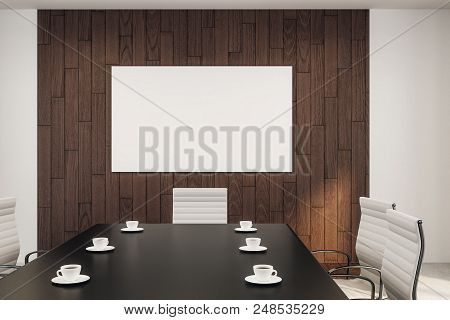 Blank White Poster On Wooden Wall In Conference Room With Black Meeting Table And Six Coffee Cups On
