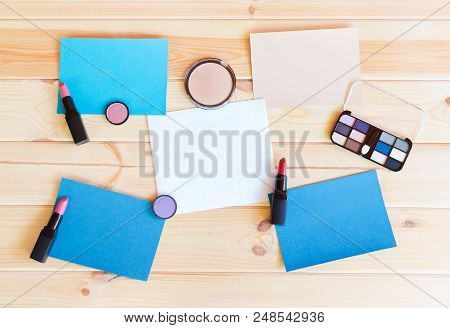 Paper Cards And Makeup Cosmetics On Wooden Background