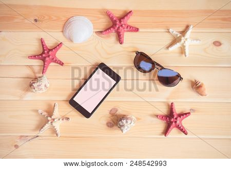 Summer Vacation Concept. Sunglasses, Smartphone, Starfishes And Seashells On Wooden Background.