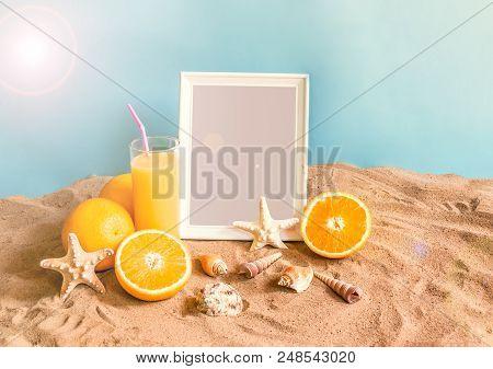 Glass Of Orange Juice, Frame, Starfishes And Seashells On Sand Beach On Blue Backdrop. Summer Beach