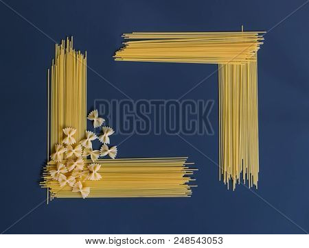 Raw Pasta Spaghetti And Farfalle In Shape Of Frame On Dark Background.