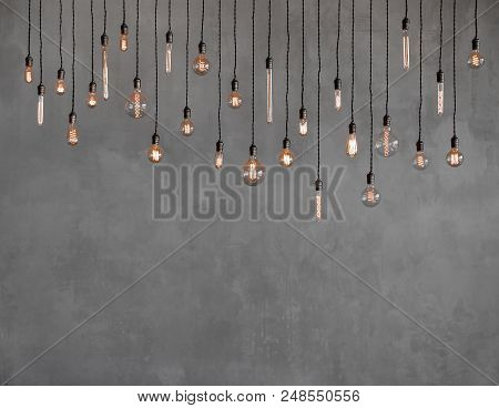Edison Retro Lamp Incandescent Bulbs On Gray Plaster Wall Background In Loft. Concept Vintage Style.