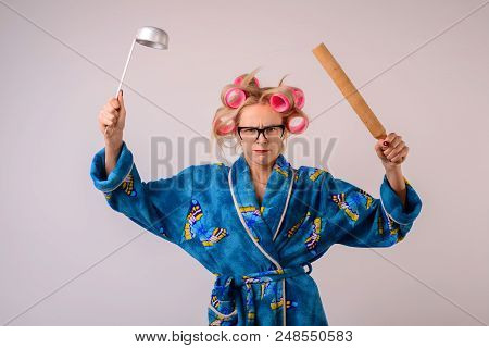 Harsh Housewife In A Dressing Gown And Curlers With A Ladle In Her Hand.