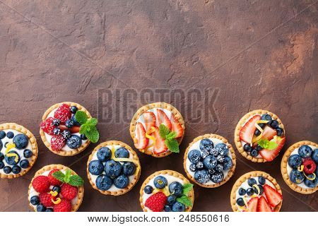 Delicious Berry Tartlets Or Cake With Cream Cheese Decorated Lemon Peel And Mint Leaf From Above. Ta