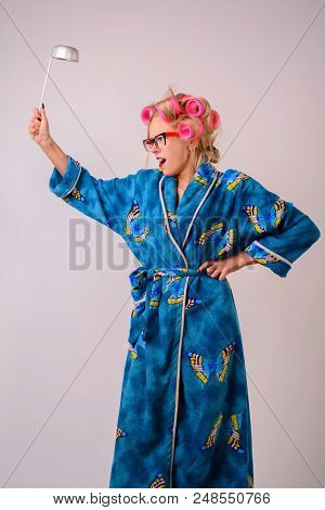 Screaming Crazy Housewife In A Dressing Gown And Curlers With A Ladle In Her Hand