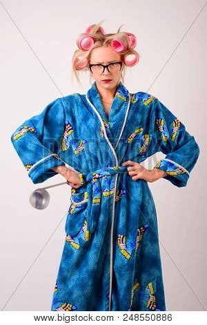 Dissatisfied Housewife In A Dressing Gown And Curlers With A Ladle In Her Hand.