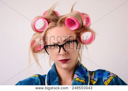 Close-up Portraits Housewife In A Bathrobe And Curlers. Looking At The Camera With One Eyebrow Raise