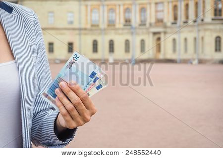 Euro Banknotes In Hand On The Background Of Attractions. Travel Concept Of The Cost Of Excursions, T
