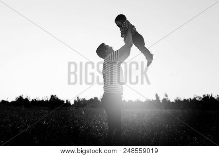 Father Playing With His Little Son In Flower Field At Sunset.