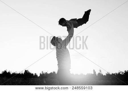 Father And Son Playing In Field At The Sunset Time. People Having Fun On The Field. Concept Of Frien