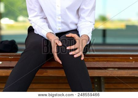 Businesswoman Is Holding Her Aching Knee While Sitting On A Bench
