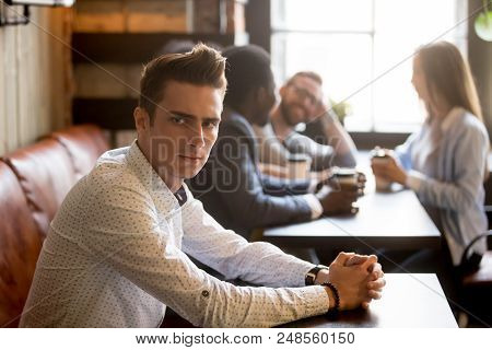 Sad Millennial Man Not Looking At Multiracial Friends Smiling And Having Fun Drinking Coffee In Cafe