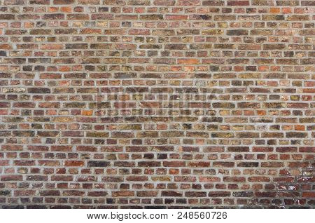 Close-up of a Old Stone Wall with brown coloured Stones.  Front View of a old Brick Wall with different colored Stones. Natural Backgrounds, Textures and Stones.