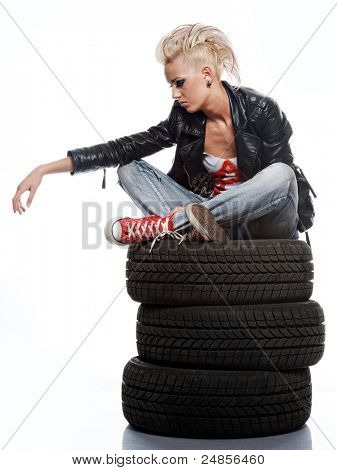 Punk girl sitting on tires.