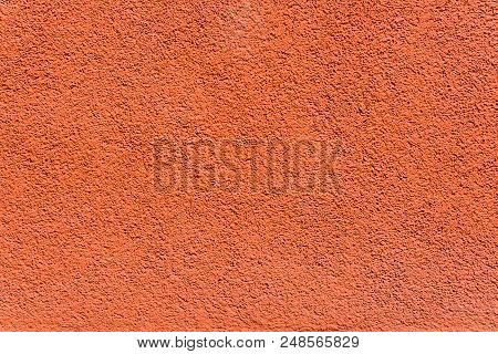 Close-up Of A Modern Orange Colored Stone Wall. Front View Of A Terracotta Colored Stone Facade. Nat
