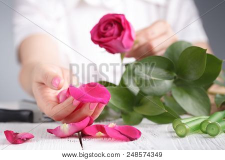 Florist Makes A Bouquet On White Wooden Table