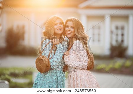 Positive And Adorable Girls Smiling And Posing In Rose And Blue Flowery Dresses. Young Beautiful Lad