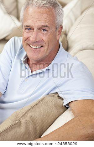 glückliche und gesunde senior Man sitzen auf einem Sofa zu Hause lächelnd und glücklich
