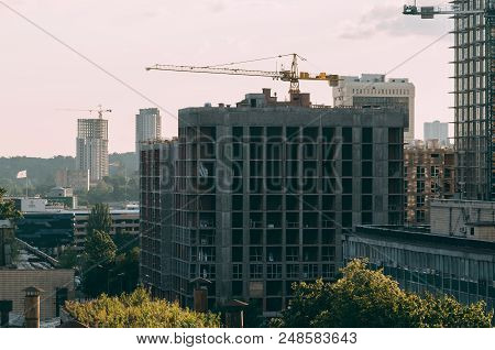 Construction of a high-rise building with a crane. Building construction using formwork. The construction crane and the building against the blue sky poster