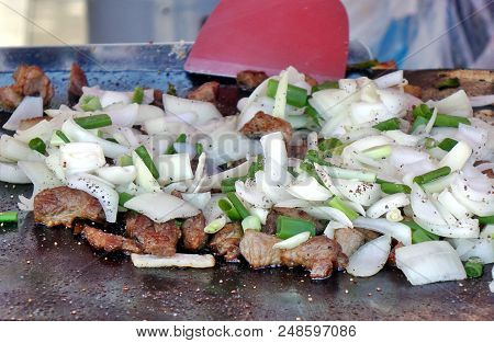 An Outdoor Vedor Cooks Meat, Onions And Leeks On A Teppanyaki Griddle