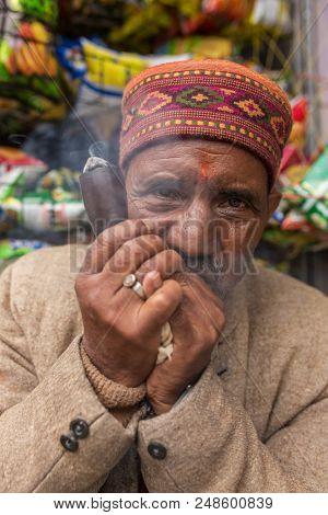 Vashisht, India - May 26, 2017: Portrait of an unidentified man in traditional himachali hat smoking chillum in Vashisht village, Himachal Pradesh, India.