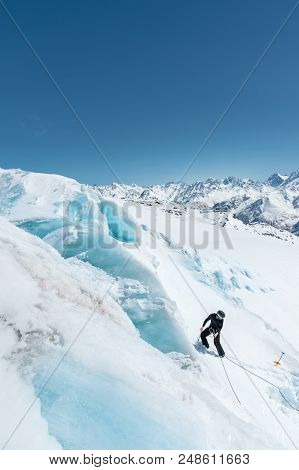 A professional mountaineer in a helmet and ski mask on insurance makes a nick-hole in the glacier against the backdrop of the Caucasian snow-capped mountains. poster