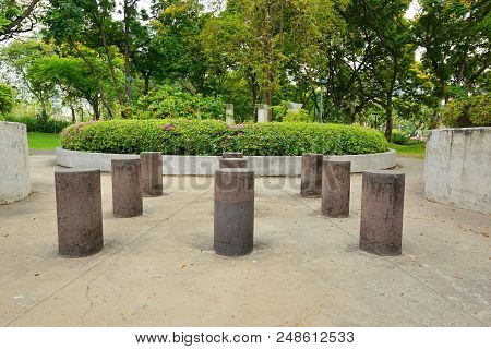Small Poles With Tree And Flowers In The Benjakiti Park At Bangkok, Thailand, Space For Your Text.