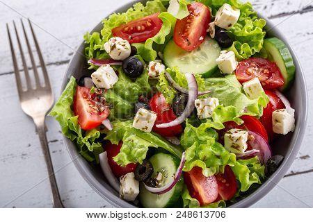 Fresh Greek Salad Served In Bowl With Fork.