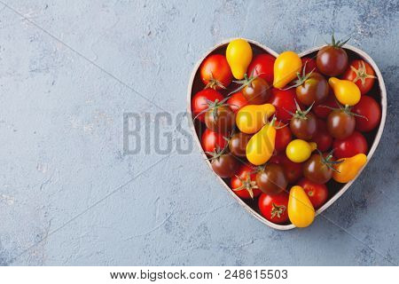 fresh delicious tomatoes in heart-shape bowl - fruits and vegetables
