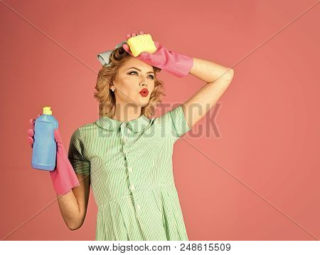 Household chores. Housekeeper in uniform with clean spray, sponge. Retro woman cleaner on pink background. Cleanup, cleaning services, wife, gender. Cleaning, retro style purity poster