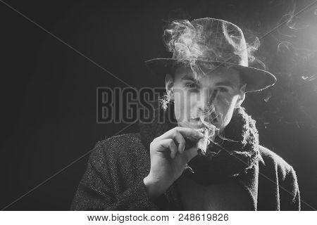 Mysterious Man. Man In Coat, Hat Smoking Cigar, Dark Background. Macho On Mysterious Face, Detective