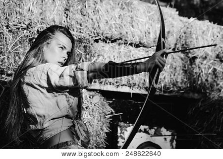 Lessons Of Shooting A Bow. Girl Or Cute Woman, Archer Or Hunter, With Long Hair Shooting With Bow An
