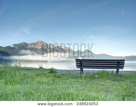 Bench Under A Tree On A Lake Shore. Mountains At Background. Take A Rest Near Blue Green Lake.  Beau