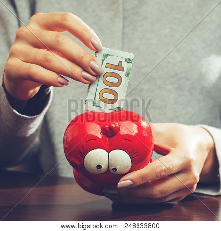 Woman Putting One Hundred Euro Banknote In A Funny Red Moneybox, Toned Image. Concept Of Future, Bus