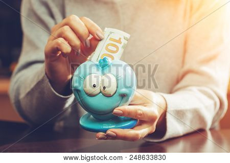 Woman Putting One Hundred Euro Banknote In A Funny Blue Moneybox In Rays Of The Sun, Toned Image. Co