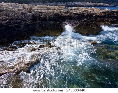 Aerial above waves crashing against coastline rocks