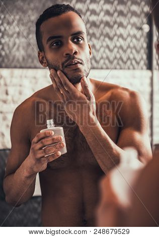Young Afro American Man Applying Aftershave Lotion And Looking Into Mirror In Bathroom At Morning. P