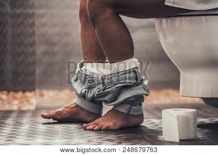 Close Up. Handsome Young Afro American Man Sitting On Toilet In Bathroom At Morning. Personal Mornin