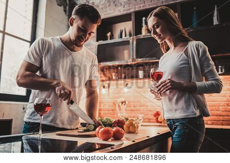 Young Couple Cooking Dinner And Drink Red Wine. Romantic Dinner In Modern Kitchen. Preparing Food On