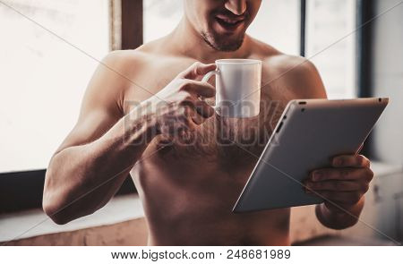 Close Up. Bare-chested Man With Tablet Pc And Coffee. Man With Bare Torso. Using Portable Digital De