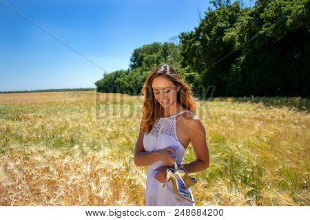 Beautiful Woman, Bride With Blue Eyes And Brown Hair Walks Through Corn Field On A Sunny Summer's Da