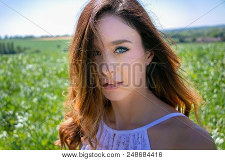 Beautiful Woman, Bride With Blue Eyes And Brown Hair Walks Through Crop Field On A Sunny Summer's Da