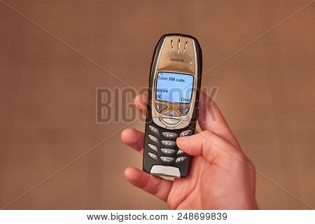 BUDAPEST, HUNGARY - MARCH 01, 2018: Nokia 6310i cellphone turning on, entering 4 digit PIN code. The 6310i was a very popular corporate phone after its introduction in 2002