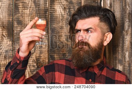 Man Holds Alcohol Cocktail On Wooden Background. Suspicious Drink Concept. Barman With Beard And Ser